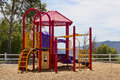 Playground on a hill small sits up with fence and mountain range in the background Royalty Free Stock Photos