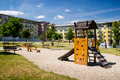 Playground in nature in front of row of newly built block of flats Royalty Free Stock Photo