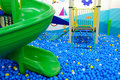 Playground where is full of little plastic balls with green slider Royalty Free Stock Photo