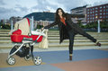 Playing with baby outdoors stroller and funny mom Royalty Free Stock Photos