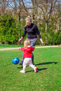 Playing with a ball cheerful mother and toddler in spring city park Royalty Free Stock Photos
