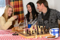 Playing chess winter chalet friends laughing cosy spend holiday Royalty Free Stock Photography