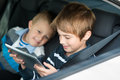 Playing children through ipad touchscreen inside the car Stock Photography