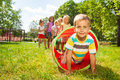 Playing crawling though tube on the lawn group of children friends play with with little blond cute little boy out of pipe with Royalty Free Stock Image