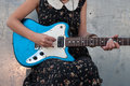 Playing electric guitar girl strumming outdoors Royalty Free Stock Photography