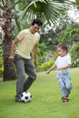 Playing football vertical image of a father with his little son on the backyard Royalty Free Stock Photography