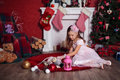 Playing girl near christmas tree in rose dress and lace gloves sitting on a carpet and Royalty Free Stock Images
