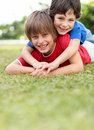 Playing on grass - Boy lying on his bother's back Royalty Free Stock Image