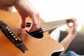 Playing guitar close up man acoustic at home hand Royalty Free Stock Photo