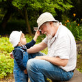 Playing with hats grandchild and grandfather having fun outdoors Royalty Free Stock Photo