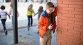 playing hide and seek. boy closed eyes his hands standing at brick wall Royalty Free Stock Photo
