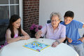 Playing ludo with grandma young and old grandchildren their ninety years old Royalty Free Stock Image