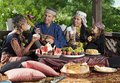 Playing mandolin the head of the family while having breakfast whole family dressed in central asian clothes Stock Images