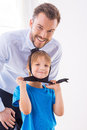 Playing with necktie cheerful little boy of his father standing near him and smiling at camera Royalty Free Stock Image