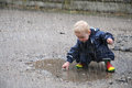 Playing in a puddle little boy with rain wear and rubber boots Royalty Free Stock Photography