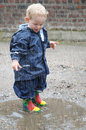Playing in a puddle little boy with rain wear and rubber boots Royalty Free Stock Photos
