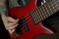 Playing on red bass guitar Stock Photo