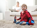 Playing with rocket cute superhero boy paying toy in the living room his mother on background Royalty Free Stock Image