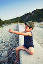 Playing with rocks boy on riverbanks outdoors in a remote location Stock Photos