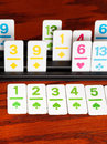 Playing in rummy card game rack on wooden board Stock Images