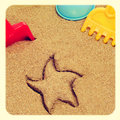 Playing in the sand image of a starfish shaped mark and shovels and rakes of different colors with a retro effect Royalty Free Stock Images
