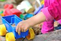 Playing at sandpit children hand keep the plastic carriage toy Stock Image