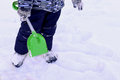 Playing in the snow with a shovel walking fresh air image of child dressed warm jacket and pants boy stands toy middle of Royalty Free Stock Photo
