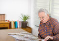 Playing solitaire old man with cards at dining table Royalty Free Stock Images