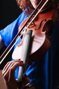 Playing the violin musical instrument with performer hands on dark background Royalty Free Stock Photo