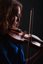 Playing the violin musical instrument with performer hands on dark background Stock Images