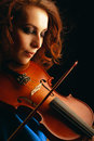 Playing the violin musical instrument with performer hands on dark background Stock Image