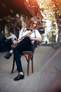 Playing young attractive girl in white shirt with a saxophone sitting near caffe shop - outdoor in sity. Sexy young woman with sax Royalty Free Stock Photo