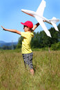 Playtime pilot a side view of a typical young boy out in a grassy field in the sunshine playing with a toy airplane trees in Stock Images