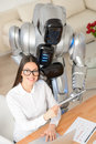 Pleasant girl and robot working in the office like our work top view of smiling content woman sitting at table with who is Royalty Free Stock Photography