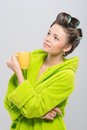 Pleasant housewife half length portrait of young wearing curlers and green wrapper holding yellow cup of tea and dreaming about Stock Photography