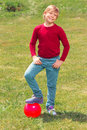 Pleasant little boy playing with ball play me full length of nice smiling holding hands in pockets and keeping one leg while Royalty Free Stock Photos