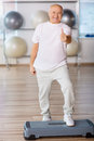 Pleasant senior man practicing step aerobics on the edge of positivity cheerful smiling thumbing up and while feeling glad Royalty Free Stock Images
