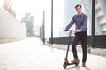 Pleasant smiling man riding a kick scooter Royalty Free Stock Photo