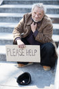 Please help depressed senior tramp in dirty wear sitting on stairs and holding poster Stock Photos