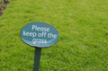Please keep off the grass sign close image of a on a freshly mowed lawn informing public that they refrain from stepping on Stock Images