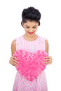 Pleased black hair model holding a pink heart shaped pillow on white background Stock Photo
