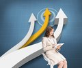 Pleased businesswoman using a tablet pc sitting on a bar chair composite image of in front of arrows blue background Stock Photography