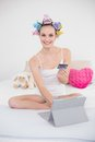 Pleased natural brown haired woman in hair curlers shopping online with her tablet pc bright bedroom Royalty Free Stock Photo
