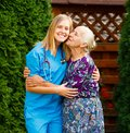 Pleased senior patient lovely being with homecare services kissing her doctor Royalty Free Stock Photo