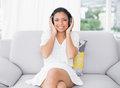 Pleased young dark haired woman in white clothes listening to music a living room Royalty Free Stock Photos