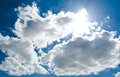 Pleasent blue sky sun under clouds Royalty Free Stock Image