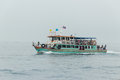 The pleasure craft with passengers onboard under the flag of thailand floats on water Stock Photo
