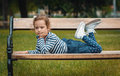 Pleasure little girl lying on bench in a park repose or relaxing in the nature Royalty Free Stock Photos