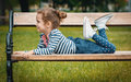 Pleasure little girl lying on bench in a park repose or relaxing in the nature Royalty Free Stock Image