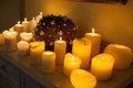 Plenty of lighted candles and decoration on commode Royalty Free Stock Photography